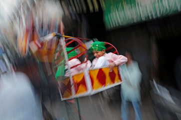 A Muslim boy enjoys a ride on a swing during a religious procession to mark Eid-e-Milad-ul-Nabi, or birthday celebrations of Prophet Mohammad, in the old quarters of Delhi