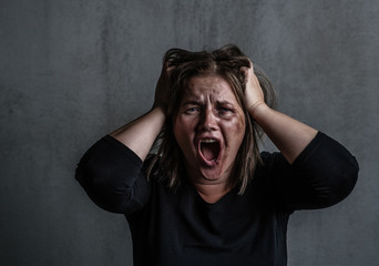 Angry young woman victim of domestic violence and abuse having nervous breakdown screaming