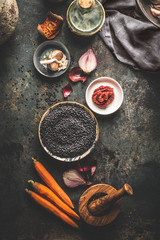 Black lentils with cooking ingredients for tasty vegan dishes on dark background. Top view. Healthy vegetarian eating concept. Horizontal banner. Plant based protein source. Top view