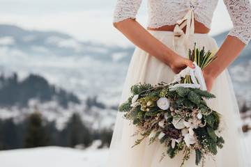 Beautiful bride in a white wedding dress holding her wedding bouquet in the mountains