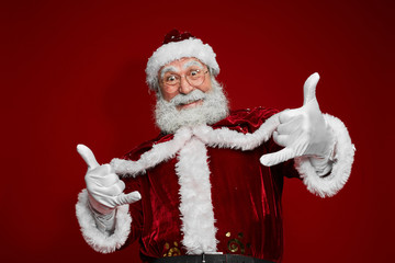 Waist up portrait of classic Santa Claus dancing and gesturing while posing against red background in studio, copy space