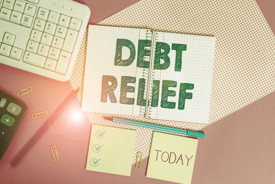 Word writing text Debt Relief. Business photo showcasing a reduction in the amount of debt that a country has to pay Writing equipments and computer stuffs placed above colored plain table