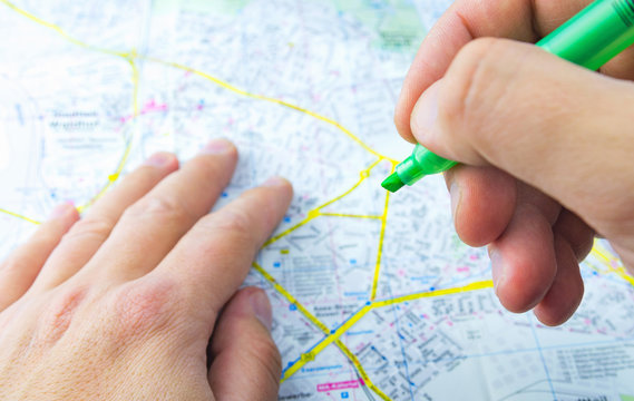 Green highlighter in the hands of a traveler on a background of a city map. Man planning an excursion route. Close-up, selective focus.