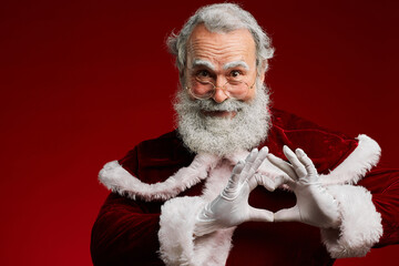 Waist up portrait of smiling Santa Claus making heart shape with hands while standing against red background in studio, copy space