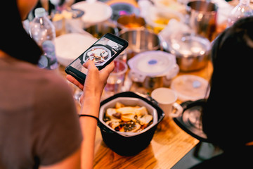 Female Friends having dinner party taking picture of food post on social media.