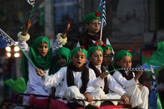 Children wave flags and chant religious slogans during a procession to mark Eid-e-Milad-ul-Nabi, or birthday celebrations of Prophet Mohammad, in Lahore,