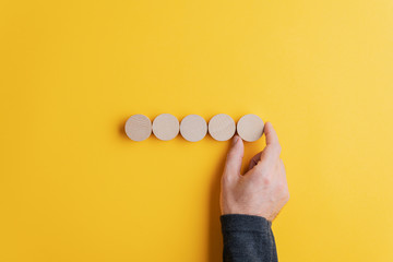 Male hand placing five blank wooden cut circles in a row