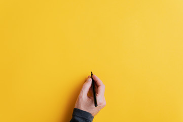Male hand writing on a blank yellow surface with black marker