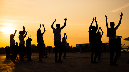 Unrecognizable people silhouette dancing on city festival at sunset. Street dance, holiday, summer and urban culture concept Fototapete