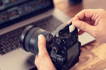 Photographer inserting or removing a memory card in professional camera