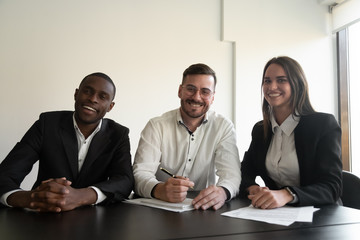 Headshot of smiling diverse employees look at camera in office