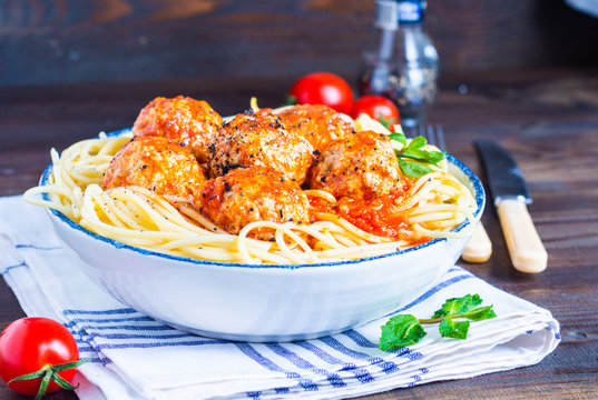 meatball in fresh tomato sauce on a bed of freshly cooked spaghetti