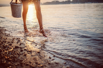 Cropped picture of female's legs walking in water. Woman holding picnic basket in hands. In background is sun.