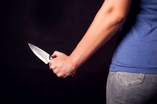 Woman with knife behind the back. People, family violence and crime concept