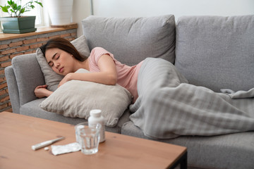 Young asian woman have sick relaxing and sleeping on sofa with pillow after taking medicines with glass of water,pack of pills and digital thermometer on table at home