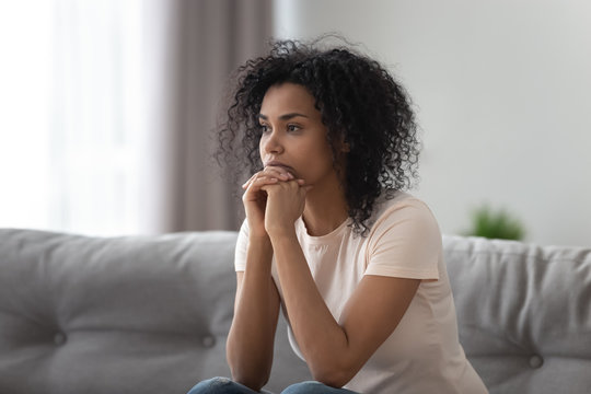 Upset African American woman thinking about problem at home alone