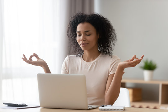 Calm African American woman meditating at desk with laptop