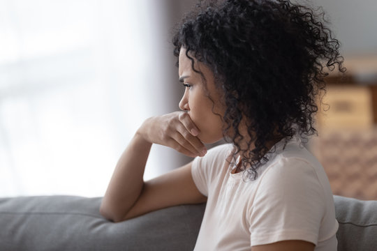 Upset African American woman thinking about problems close up