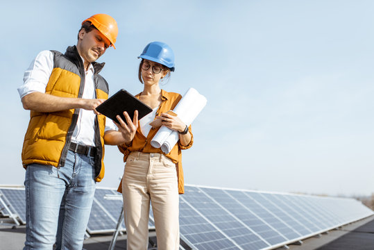 Two engineers or architects examining solar power plant with a digital tablet. Solar station development concept