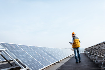 View on the rooftop solar power plant with mann walking and examining photovoltaic panels. Concept of alternative energy and its service