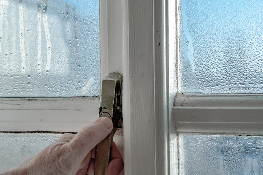 Homeowner seen unlocking a wooden framed window in early morning. Condensation has built up on the glass, which can cause breathing issues for sick people.