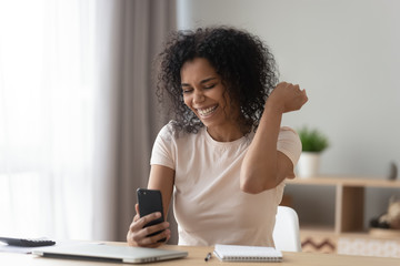 Happy African American woman using phone, celebrating success