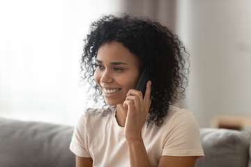 Smiling African American woman talking on phone, chatting with friend
