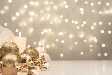 Box with golden christmas ball and candle on gold bokeh background
