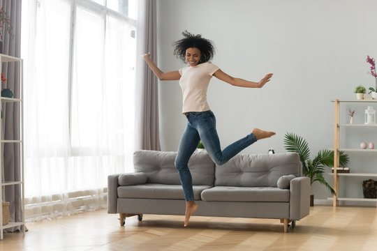 Happy African American woman jumping in living room, celebrating success
