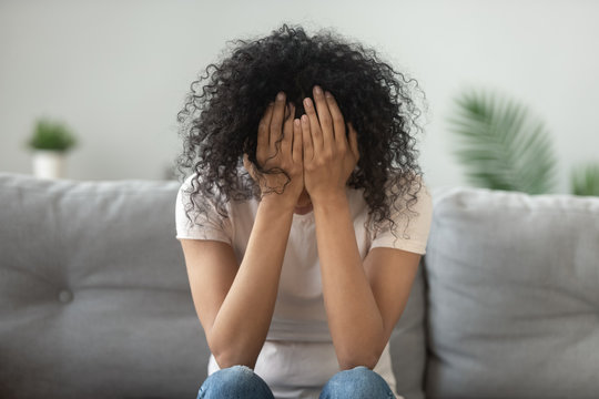 Unhappy African American woman holding head in hands, crying
