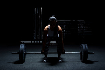 Anonymous woman bodybuilder make workout - weight lifting with barbell. Light from above, dark background.
