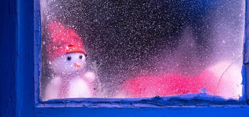 sad snowman looking through window. Window still background with ice and snow for your decoration and winter landscape of forest with snowman. Christmas time and sunny cold day.