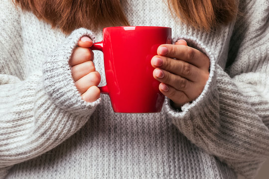 Picture of a woman's hand holding a red coffee mug