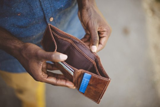 Overhead shot of a male holding his empty wallet with a blurred background