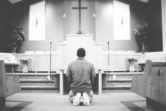 Grayscale of a male on his knees praying in the church with a blurred background