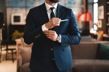 Handsome businessman adjusting his sleeves while standing in modern office Wall mural