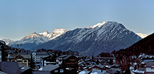 Foto auf AluDibond Arktis Traditional wooden Hotels and Huts in Saas-Fee Ski Resort with morning light on mountain range in Switzerland