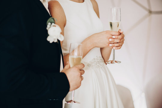 Stylish wedding couple holding champagne glasses and toasting at wedding reception in restaurant, cropped view. Bride and groom holding drinks and cheering, listening to toast. Luxury banquet