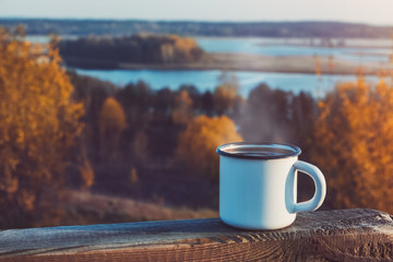 Photo sur Aluminium Marron chocolat Enameled cup of coffee or tea on autumn landscape outdoors.