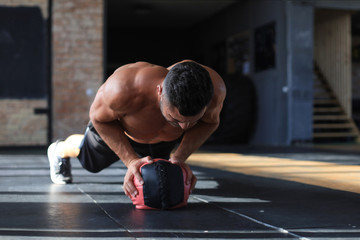 Fit and muscular man exercising with medicine ball at gym. Wall mural