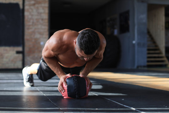 Fit and muscular man exercising with medicine ball at gym.