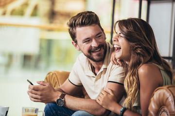 Beautiful young couple using a smartphone and smiling while sitting in the cafe