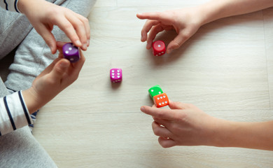 Two clever children study mathematics playing with dices on the floor