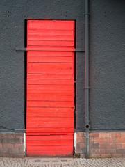 red door in a gray wall_vertical