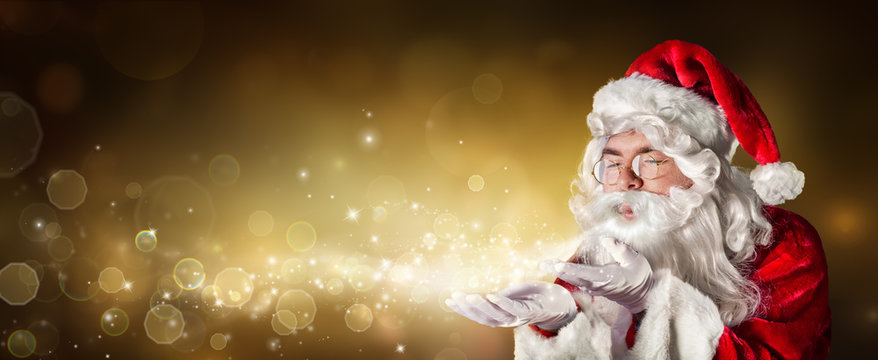 Santa Claus Blowing Magic Christmas Lights In Golden Background