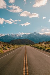 Vertical shot of a road with the magnificent mountains under the blue sky captured in California