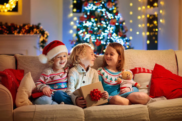 Child at Christmas tree. Kids at fireplace on Xmas