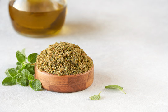 Mixed spice zaatar or zatar in wooden bowl with olive oil
