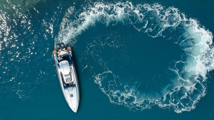 Aerial drone  top down photo of luxury rigid inflatable power boat or RIB boat manoeuvring in high speed in open ocean deep blue sea Wall mural