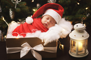 Cute newborn baby wearing Santa Claus hat is sleeping in the Christmas gift box